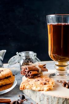 Biscoitos com gotas de chocolate, ñ de chá, canela, anis em fundo escuro