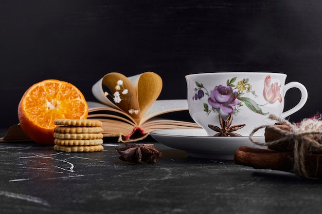 Biscoitos com laranja e uma xícara de chá.