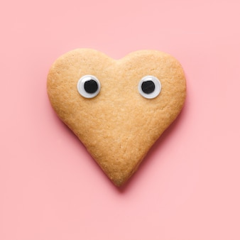 Biscoitos com olhos em forma de coração para dia dos namorados em rosa. conceito de comida. vista de cima.