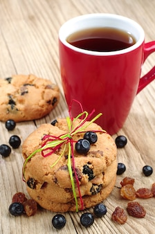 Biscoitos com passas e mirtilos, amarrados com fita colorida e xícara de chá