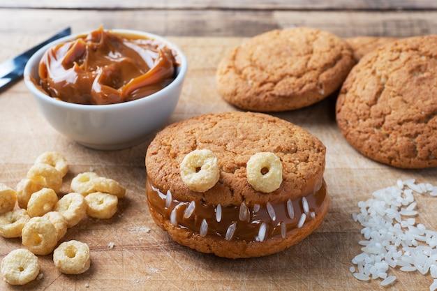 Biscoitos com pasta de creme em forma de monstros para a celebração do halloween. caras caseiras engraçadas feitas de biscoitos de aveia e leite condensado fervido.