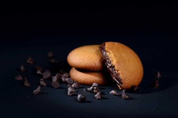 Biscoitos com recheio de creme de chocolate. cookies de chocolate com creme. biscoitos de chocolate marrons com recheio de creme sobre fundo preto.