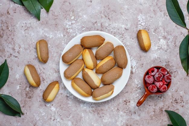 Biscoitos com recheio de geléia de framboesa e framboesas congeladas na luz de fundo, vista superior