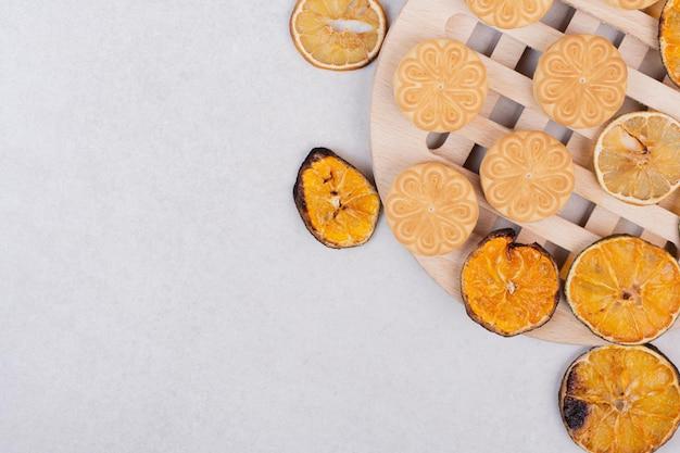 Biscoitos com rodelas de laranja no prato de madeira