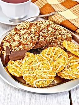 Biscoitos com sementes de gergelim e sementes de girassol, biscoitos de chocolate, chocolate em uma bandeja de metal, xícaras, guardanapos em um fundo de quadro de luz