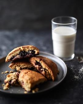 Biscoitos com uma geléia de baga e um copo de leite com um fundo desfocado