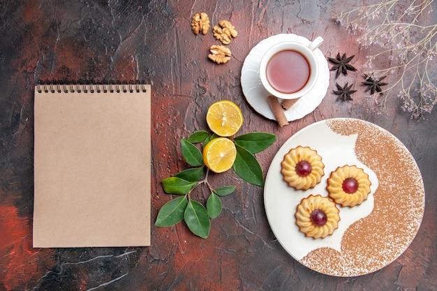 Biscoitos com uma xícara de chá em um bolo de biscoito de açúcar de mesa escura com vista de cima