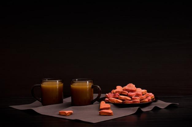Biscoitos com vermelho em forma de coração, duas canecas de café com leite