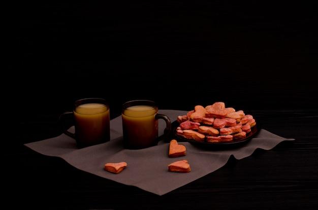 Biscoitos com vermelho em forma de coração, duas canecas de café, dia dos namorados