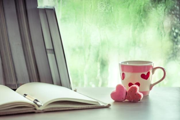 Biscoitos cor-de-rosa do coração e copo de café com caderno no fundo da janela do dia chuvoso no tom de cor vintage