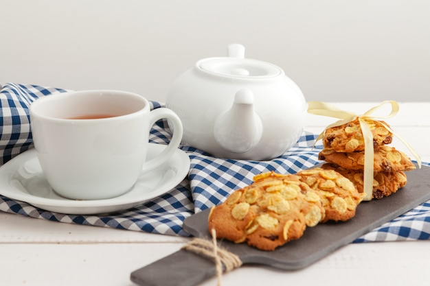 Biscoitos crocantes caseiros e chá em uma mesa de madeira