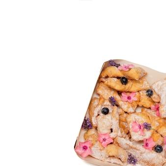 Biscoitos crocantes de palhas quebradiças polvilhadas com açúcar de confeiteiro decorado com flores de frutas vermelhas. cozimento caseiro. conceito de padaria, serviço de comida estética. vida doce. foto de close-up. copie o espaço. isolado