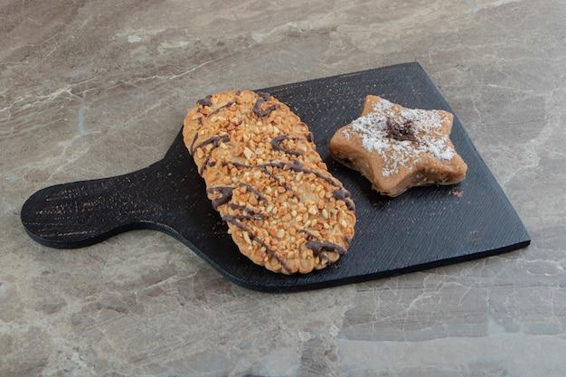 Biscoitos crocantes e biscoitos em forma de estrela no tabuleiro escuro