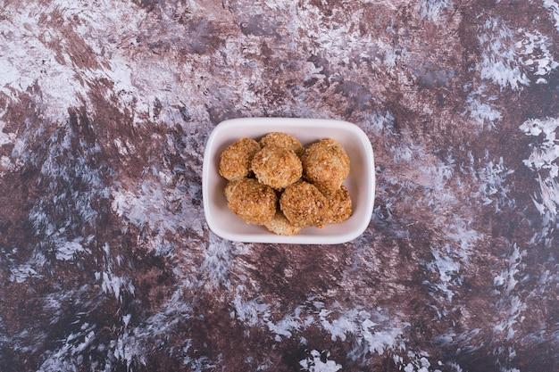 Biscoitos crocantes em pires de cerâmica branca, vista de cima