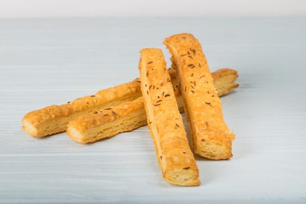 Biscoitos crocantes salgados com sementes de gergelim sobre fundo branco