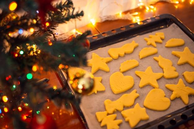 Biscoitos crus na assadeira perto da árvore de natal decorada antes de assar
