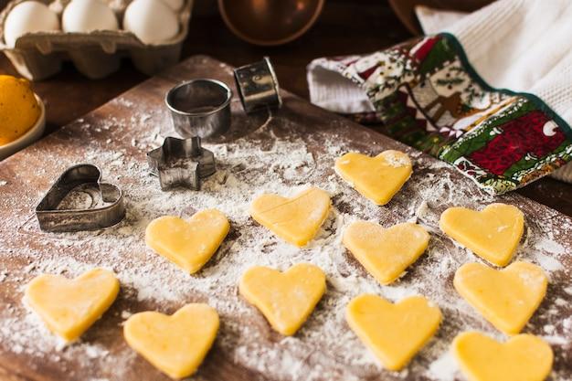 Biscoitos crus perto de cortadores de biscoito e toalha