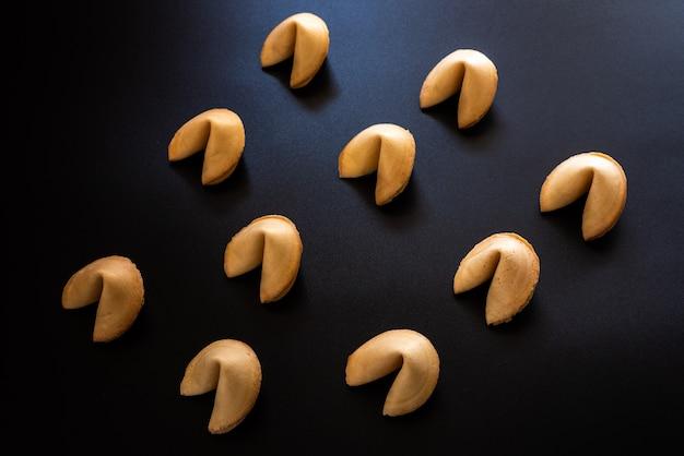 Biscoitos da sorte em fundo escuro dispostos simetricamente
