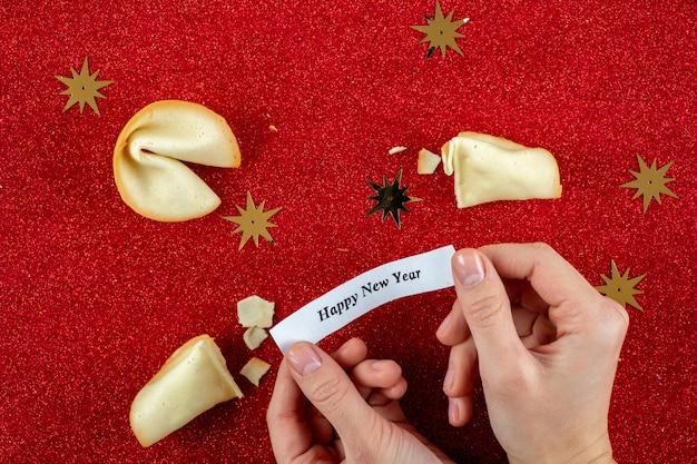 Biscoitos da sorte na mão com os cumprimentos de ano novo