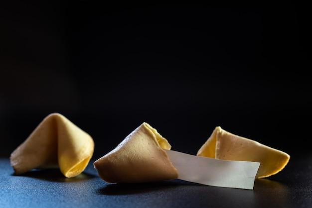 Biscoitos da sorte quebrados com mensagem da fortuna, isolados no fundo preto com espaço vazio para o texto.
