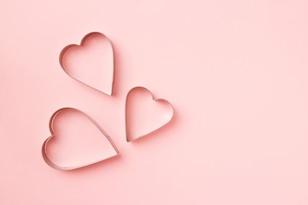 Biscoitos de 3 cortadores em forma de coração no fundo rosa pastel. cartão de dia dos namorados conceito.