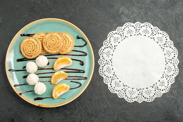Biscoitos de açúcar com balas de coco no fundo cinza.
