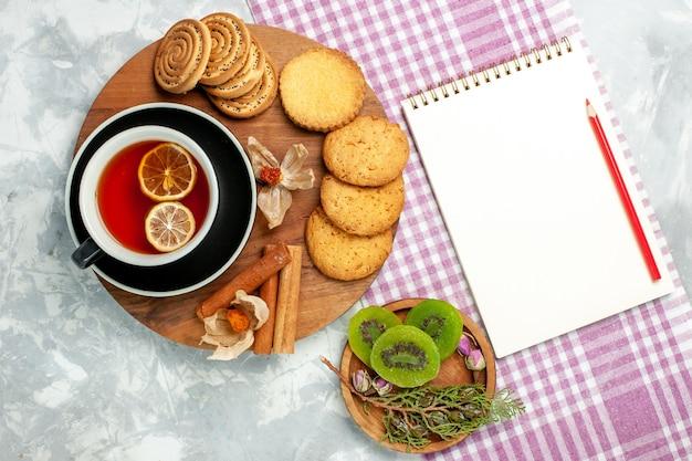Biscoitos de açúcar com uma xícara de chá e fatias de kiwi em uma mesa branca