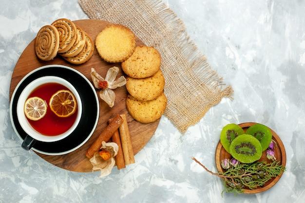 Biscoitos de açúcar com uma xícara de chá e fatias de kiwi em uma torta de biscoito de parede branca