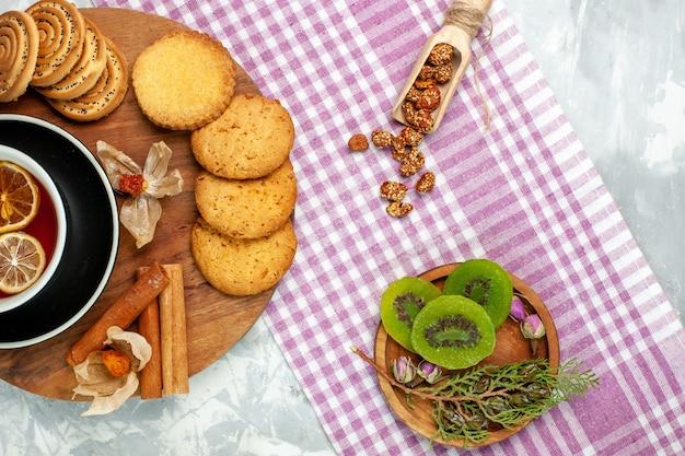 Biscoitos de açúcar com uma xícara de chá e fatias de kiwi na parede branca biscoitos de biscoito torta doce