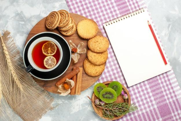 Biscoitos de açúcar com uma xícara de chá e um bloco de notas em uma torta de bolo doce de biscoitos de parede branca