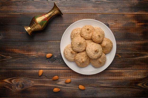 Biscoitos de amêndoa em um prato branco sobre um fundo de madeira.