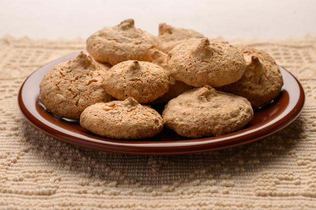 Biscoitos de amêndoa em um prato num guardanapo de linho. vista do topo. copie o espaço.