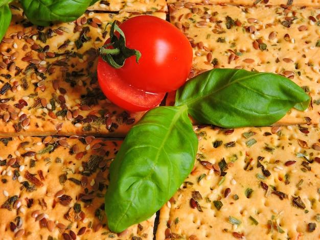 Biscoitos de aptidão com sementes de linho. tomate cereja e manjericão.