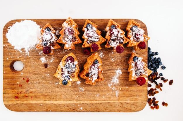 Biscoitos de árvore de natal com bagas planas leigos.