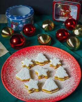 Biscoitos de árvore de natal, sino e estrela cobertos com açúcar de confeiteiro