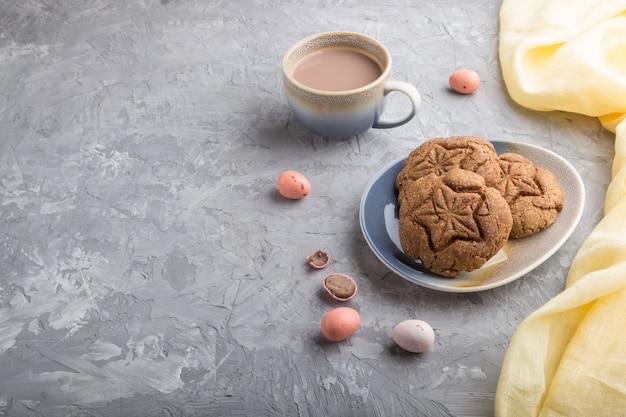 Biscoitos de aveia caseiro com uma xícara de cacau em um fundo cinza e concreto. vista lateral, copie o espaço.