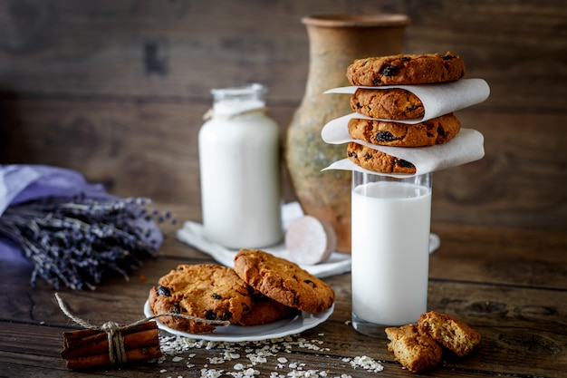 Biscoitos de aveia caseiros com nozes e passas e copo de leite no fundo escuro de madeira