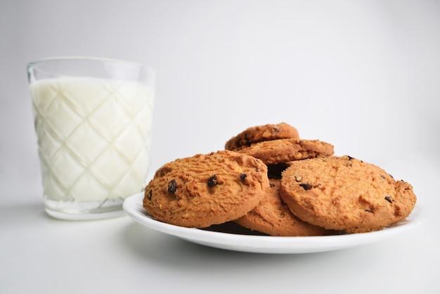 Biscoitos de aveia caseiros com pedaços de close-up de chocolate, no fundo um copo de leite.
