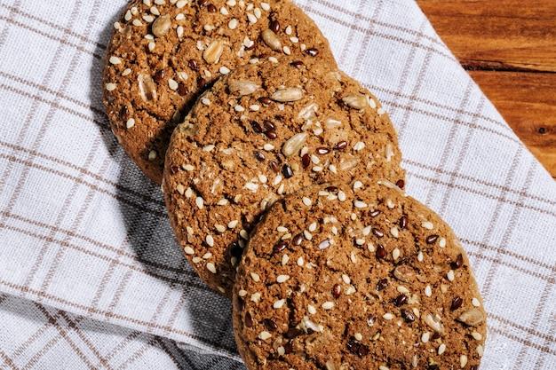 Biscoitos de aveia caseiros com sementes em guardanapo de linho natural na mesa de madeira