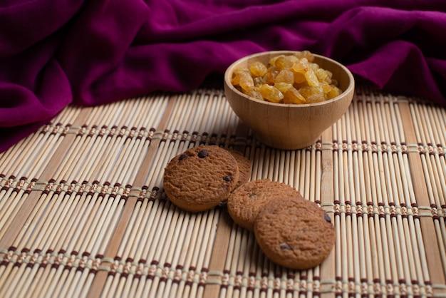 Biscoitos de aveia caseiros com uma tigela de uva passa