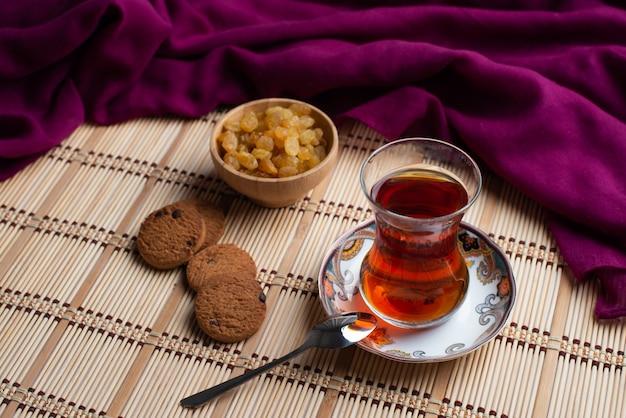 Biscoitos de aveia caseiros com uma xícara de chá e uma uva passa
