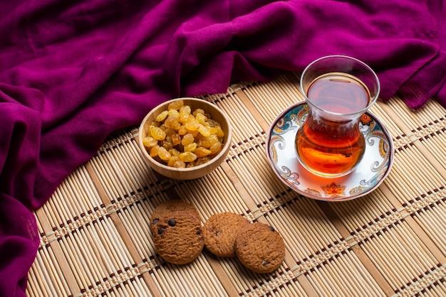 Biscoitos de aveia caseiros com uma xícara de chá turco e uma uva passa