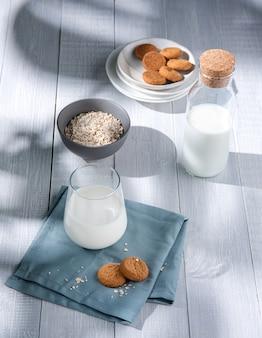 Biscoitos de aveia caseiros frescos com um copo de leite vegan em uma mesa de madeira branca. luz da manhã