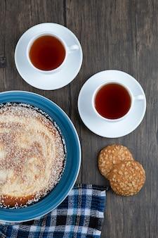 Biscoitos de aveia com cereais e sementes colocados com torta e chá sobre uma mesa de madeira.