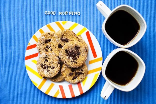 Biscoitos de aveia com chocolate num guardanapo azul e duas xícaras de café, inscrição de bom dia.