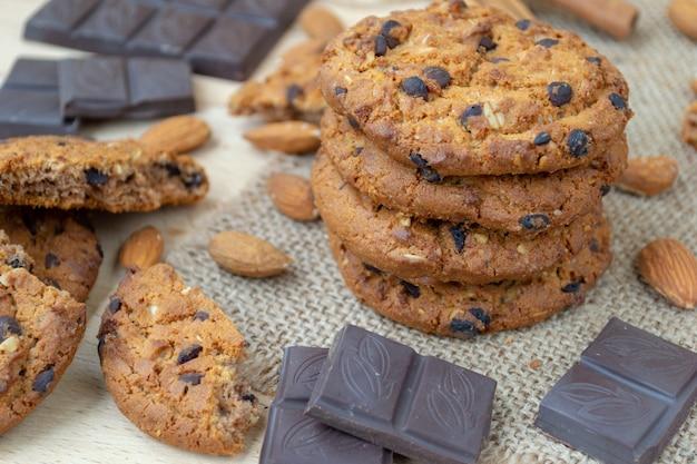 Biscoitos de aveia com chocolates e nozes em uma mesa de madeira.