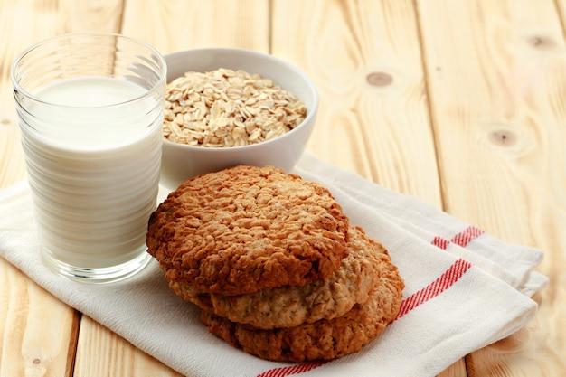 Biscoitos de aveia com flocos de aveia e copo de leite na mesa de madeira fecham