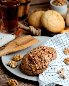 Biscoitos de aveia com nozes e uma xícara de chá aromático