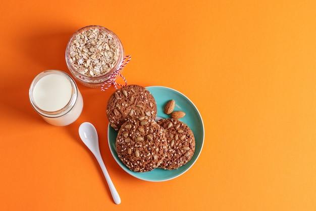 Biscoitos de aveia com nozes em um prato, copo de leite