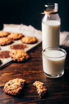 Biscoitos de aveia com passas e copo de leite no café da manhã. alguns biscoitos em papel pergaminho com garrafa